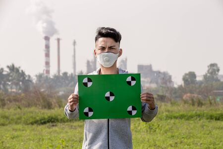 asian man hold green copy space billboard and wears protective n95 mask against air pollution standing in front of factory Stock Photo
