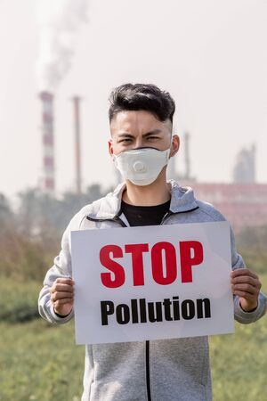 asian man hold stop pollution sign and wears protective n95 mask against air pollution standing in front of factory