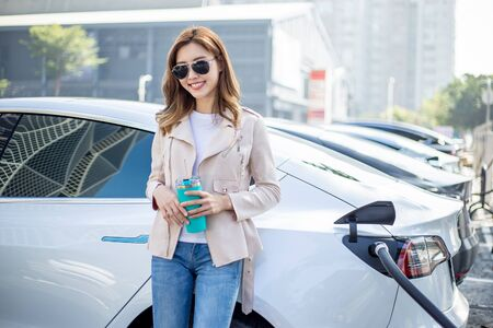 asian woman use reusable eco-friendly ecological straw drink while waiting and power supply connect to electric vehicles for charging the battery in car