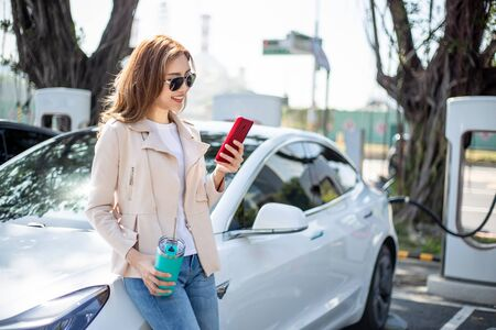 asian woman use reusable eco-friendly ecological straw drink while using smart phone and waiting power supply connect to electric vehicles for charging the battery in car