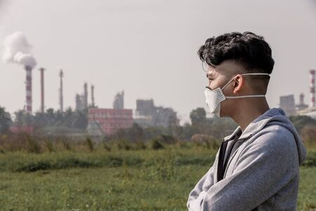 asian man look something and wears protective n95 mask against air pollution standing in front of factory