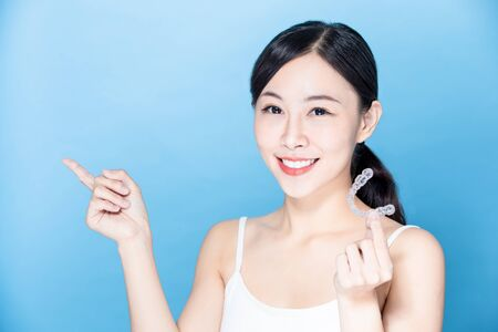 asian woman take her invisible brace on hand and point something with smile Stock Photo