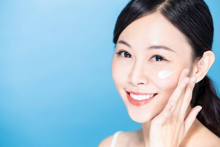 asian beauty woman apply lotion or sunscreen on her face and smile to you Stock Photo