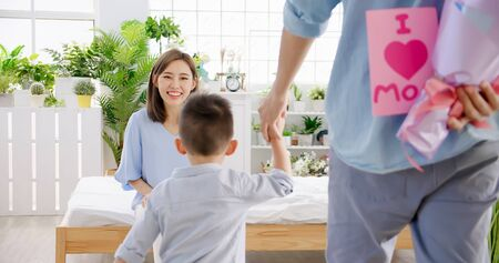 happy family - father and son are hiding flowers and card for their mother behind backs while she is sitting at home
