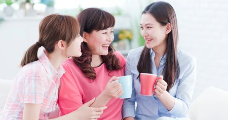 Mom and daughters drink and chat together