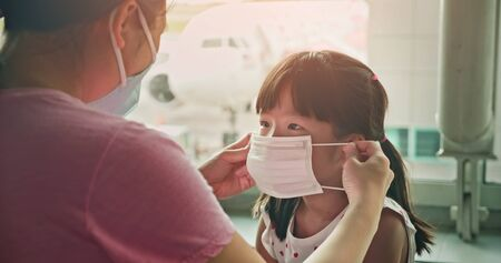 Asian parents wear masks to their children because of transmissible infectious diseases indoor in the airport Foto de archivo