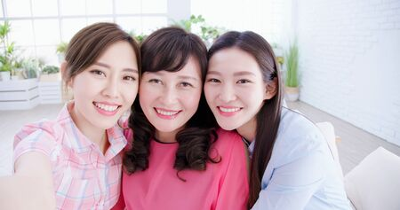 daughters and mom take selfie together happily