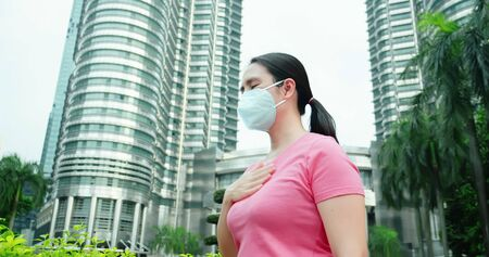asian woman feel sore throat and wears protective face mask because of transmissible infectious diseases or air pollution in Malaysia Kuala Lumpur Reklamní fotografie