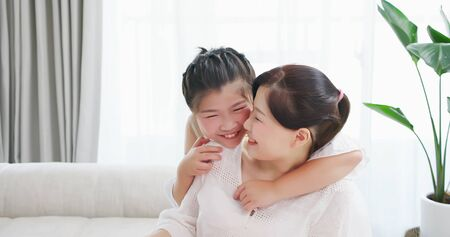 asian daughter girl whisper to mother and they smile Banque d'images