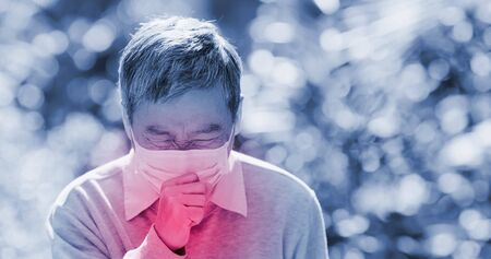 old asian man wear mask and cough outdoor because of transmissible infectious diseases or air pollution