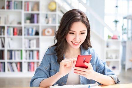 Una studentessa asiatica usa felicemente il cellulare Archivio Fotografico