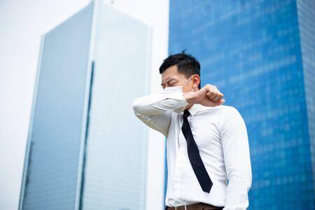 Asiatischer Geschäftsmann hustet im Ellbogen mit chirurgischem Gesichtsmaskenschutz