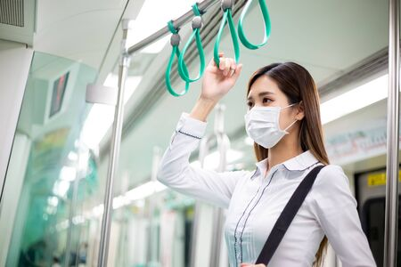 Asian businesswoman with surgical mask face protection and keep social distance while commute in the metro or train mrt