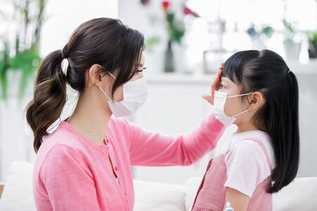 Mom touch kids forehead to check her fever condition at home