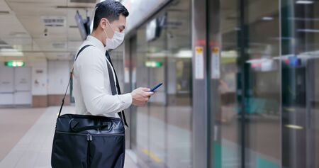 Asian business man use a smartphone with surgical mask face protection and keep social distancing while waiting in the metro or train station