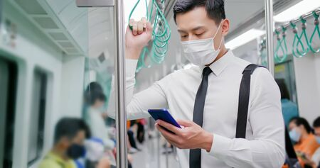 Asian business man with surgical mask face protection use a smartphone and keep social distancing to crowd while commuting in the metro or train Archivio Fotografico