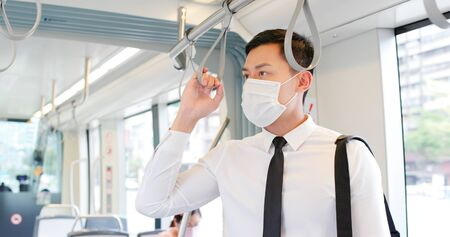 Asian business man with surgical mask face protection and keep social distancing while commuting in the metro or train Stock Photo