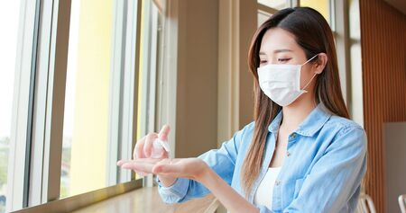 Young asian woman use sanitizer alcohol gel to dry clean her hands and wear mask