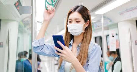 Asian woman use a smartphone with surgical mask face protection and keep social distancing while commuting in the metro or train Stock Photo