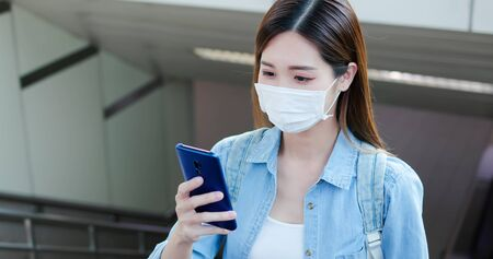 Asian woman use a smartphone while commuting with surgical mask face protection in the metro or train station