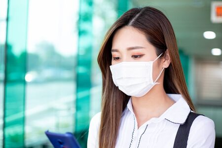 Asian woman use a smartphone while walking with surgical mask face protection in the metro or train station