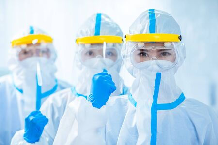 doctors look to you with fist gesture - they wear the isolation gown or protective suits and surgical face masks in the control area to prevent the spread of coronavirus