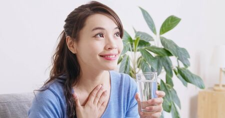 asian woman drink water and feel better at home
