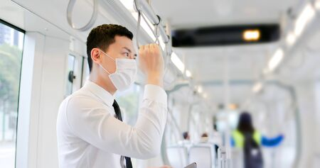 Asian business man with surgical mask face protection and keep social distancing while commuting in the metro or train
