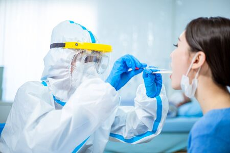 Coronavirus test - Medical worker taking a throat swab for coronavirus sample from a potentially infected woman with the isolation gown or protective suits and surgical face masks
