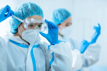 female medical worker wear protective suits and ready to take care of coronavirus patient in isolation room