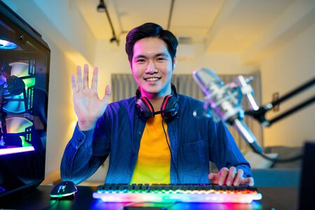 Young Asian Pro Gamer have live stream and say hi to fans happily at home