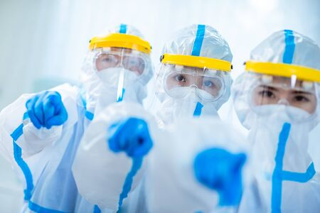 doctors point to you - they wear the isolation gown or protective suits and surgical face masks in the control area to prevent the spread of coronavirus