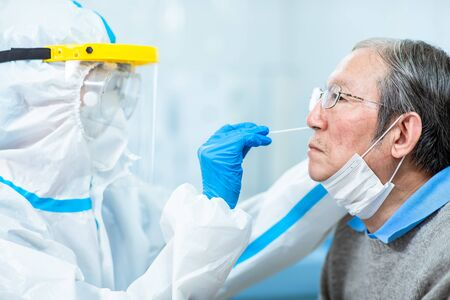 Coronavirus test - Medical worker taking a swab for corona virus sample from potentially infected elder man with the isolation gown or protective suits and surgical face masks