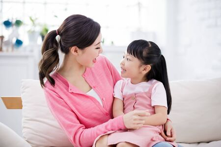 Mom hold daughter in her arm and they are talking happily