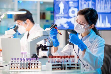 close up of microbiologist or medical worker scan blood test result Standard-Bild