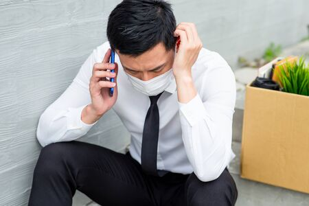 Asian business man wear face mask and speak smartphone - he is being fired because of economic downturn due to covid-19 spread all over the world