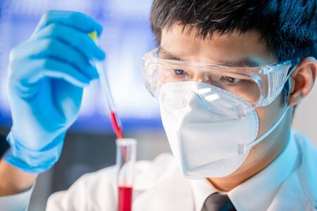 close up of microbiologist or medical worker use test tube filling with blood in the laboratory Stock Photo
