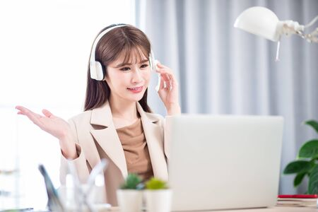 telework concept - Asian woman use computer and headphone microphone to join a video meeting at home