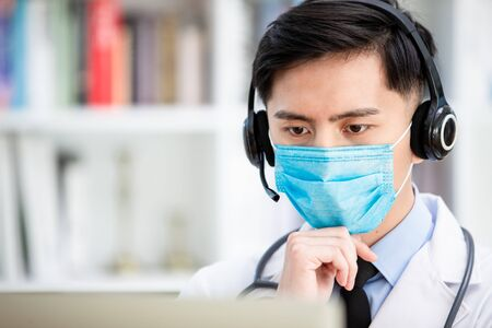 Telemedicine concept -  asian male doctor listening to patient talking symptom on the internet and he is thinking Banque d'images