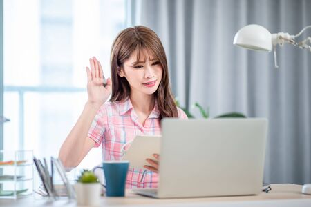 Smart asian young girl student study and raise hand to ask questions on online courses at home