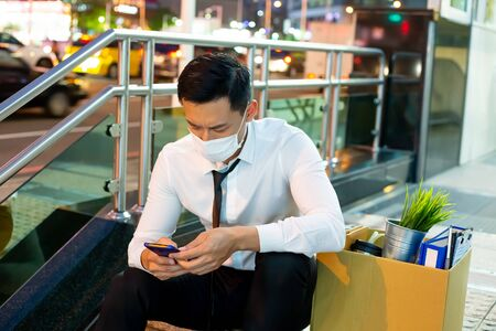 Asian business man wear face mask and search his next job - he is being fired because of economic downturn due to covid-19 spread all over the world