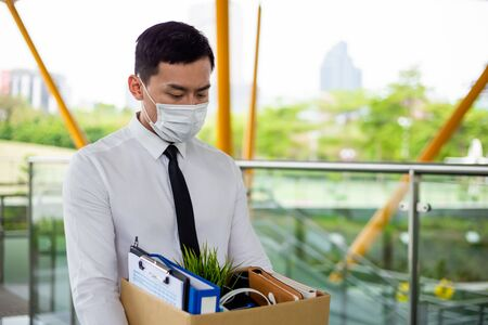 Asian business man wear face mask and he is being fired because of economic downturn due to coronavirus spread all over the world 免版税图像