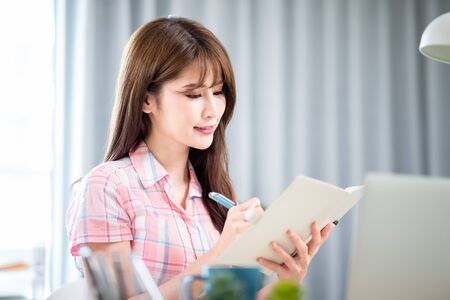 Smart asian young girl student study something during internet online courses and she writes notes with laptop computer at home