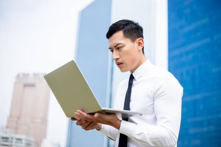 Asian business man feel depress while looking laptop and he sees the current situation of the financial market due to covid-19 spread all over the world