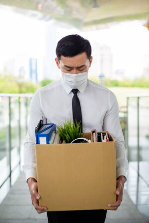 Asian business man wear face mask and he is being fired because of economic downturn due to covid-19 spread all over the world