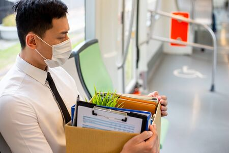 Asian business man wear face mask on the metro and he is being fired because of economic downturn due to covid-19 spread all over the world Zdjęcie Seryjne - 147341435