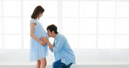 happy pregnant couple expecting baby and kiss the baby through the belly