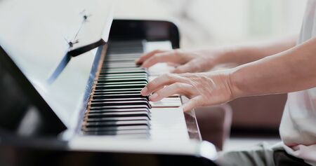 close up of asian old man practice playing the piano at home