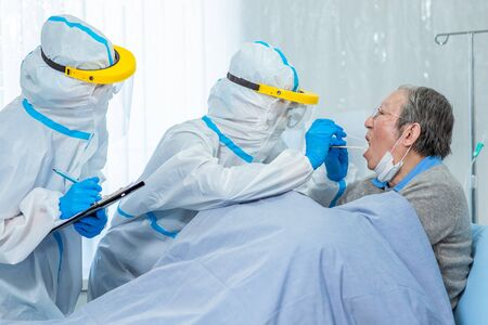 Coronavirus test - Medical worker taking a throat swab for coronavirus sample from a potentially infected elder man with the isolation gown or protective suits and surgical face masks