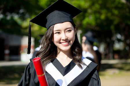 happy female graduate student holding diploma in her hand and smile Imagens